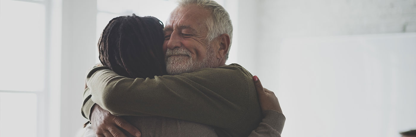 Two people hugging at a recovery support meeting